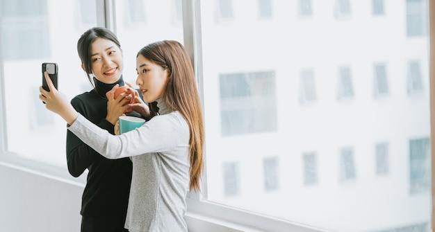 2人のアジアのビジネスウーマンが休憩中に窓際でおしゃべりをしていた