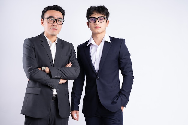 白い背景でポーズをとって2人のアジア人実業家
