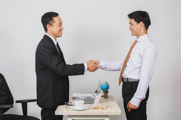 スーツを着て、取引の概念のためにオフィスの机の上で握手を結ぶ2人のアジア人ビジネスマン