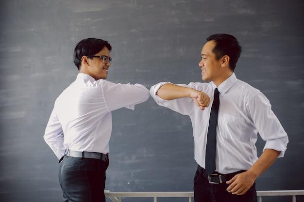コロナウイルスを回避するために肘をぶつけて白いシャツを着た2人のアジア人ビジネスマン
