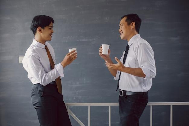 紙のコーヒーカップを持ってチャットしながら白いたわごとの2人のアジアのビジネスマン