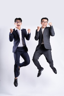 Два азиатских бизнесмена прыгают на белом фоне