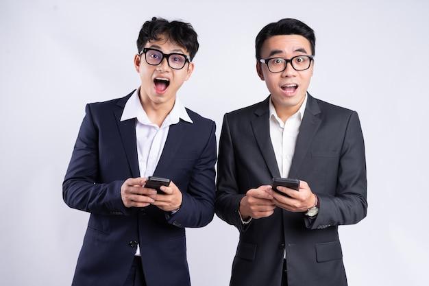 흰색 바탕에 스마트폰을 사용하는 두 아시아 사업가
