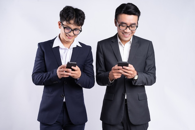 Two asian businessmen using smartphone on white background