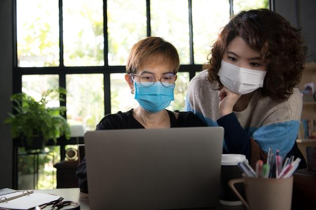 Covid-19コロナウイルスのパンデミックの間にオフィスで働いている間に外科用マスクを身に着けている隔離と社会的距離の2人のアジアのビジネスウーマン