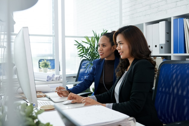 Two asian businesswomen sitting together in office at desk and looking at computer screen
