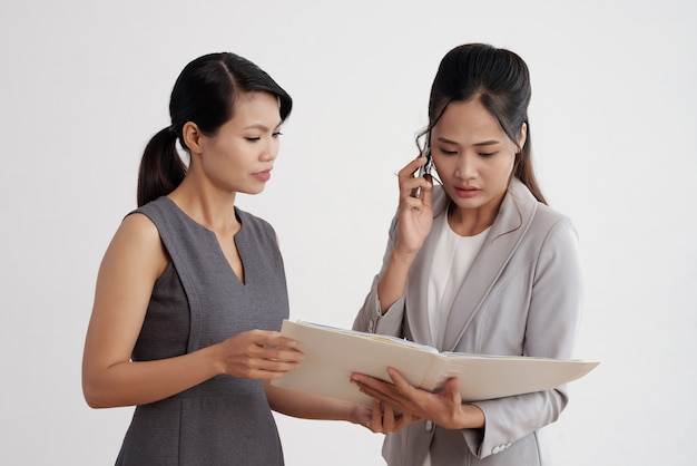 Two asian businesswomen standing together, looking at document in folder and talking on phone