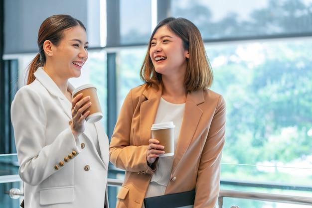 近代的なオフィスやコワーキングスペースでコーヒーブレーク中に話している2人のアジアのビジネスウーマン、コーヒーブレーク、リラックスして仕事時間、ビジネスと人々のパートナーシップの概念の後話
