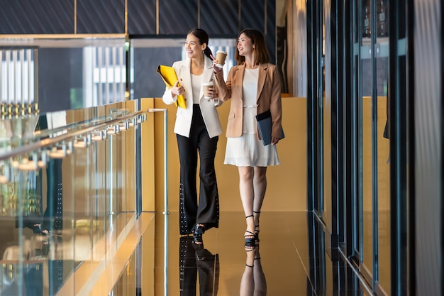 Two asian businesswomen walking and talking during coffee break in modern office or coworking , coffee break, relaxing and talking after working time, business and people partnership