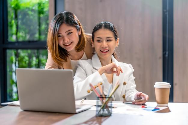 モダンな会議室、オフィスまたは作業スペース、コーヒーブレーク、パートナーおよび同僚の概念の技術ラップトップを介してパートナービジネスで働く2人のアジアのビジネスウーマン