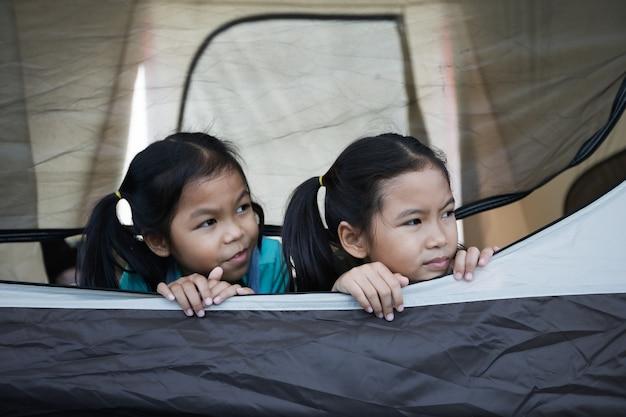 Две азиатские детские девочки лежат и играют вместе в палатке на кемпинге во время кемпинга с семьей