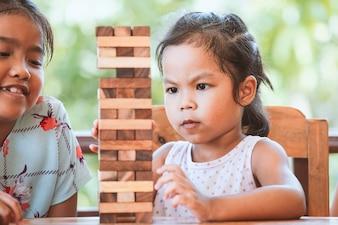 Две азиатские девочка девочка играет деревянные блоки стек игры вместе с весельем и счастьем