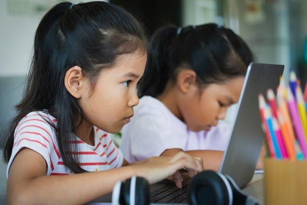 2人のアジアの子供女の子の学生が一緒にビデオ通話で先生とオンラインで勉強します。兄弟は、covid 19のパンデミックのため、検疫中にコンピューターのラップトップを使ってホームスクーリングをしています。