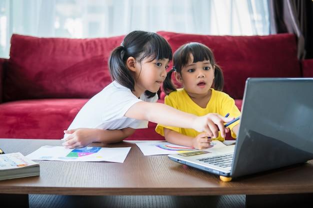 두 명의 아시아 여학생이 화상 통화로 선생님과 온라인으로 공부합니다.