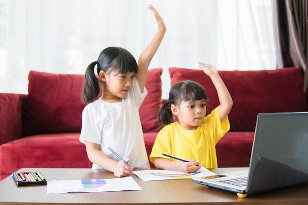 2人のアジアの子供女の子の学生が一緒にビデオ通話で先生とオンラインで勉強します。