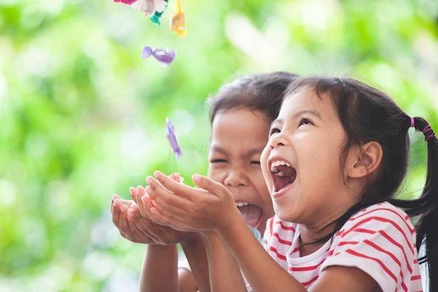 Two asian child girls having fun to catching candies falling from the sky