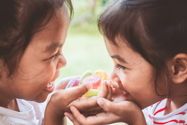 Two asian child girls holding sweet candies in thier hands and share to each other