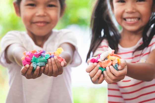 Two asian child girls holding sweet candies in thier hands