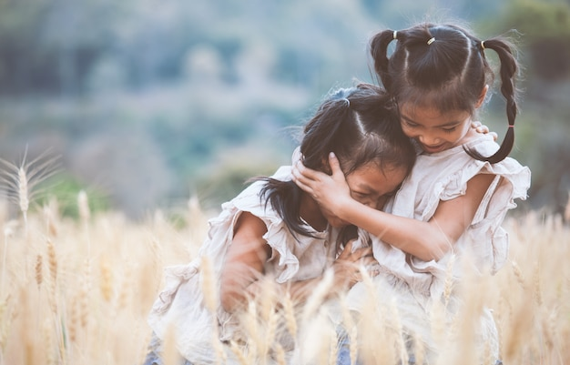 Two asian child girls hugging each other with love and playing together in the barley field