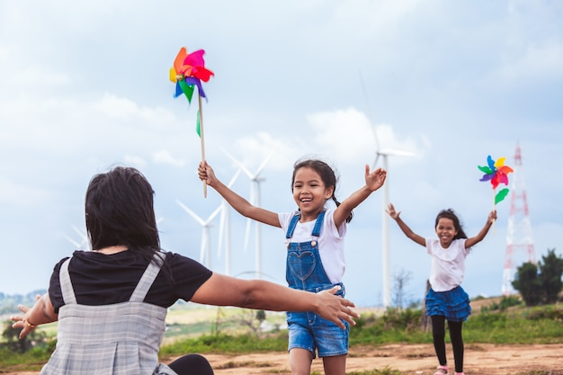 Two asian child girls playing with wind turbine toy and running to their mother to give a hug
