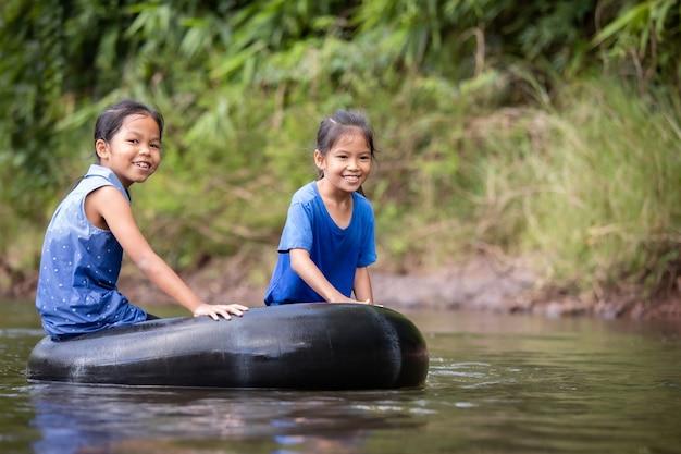 고무 링에 앉아서 함께 강에서 노는 두 아시아 아이 소녀