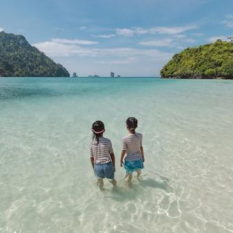 서서 바다에서 놀고 재미와 함께 아름다운 자연과 함께 즐기는 두 아시아 아이 소녀. 여름 휴가 개념.