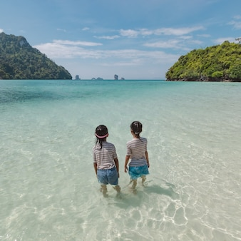 Two asian child girls standing and playing in the sea and enjoying with beautiful nature together with fun. summer holidays concept.