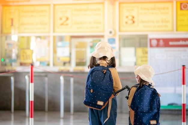 駅の切符売り場にいる2人のアジアの子供たち