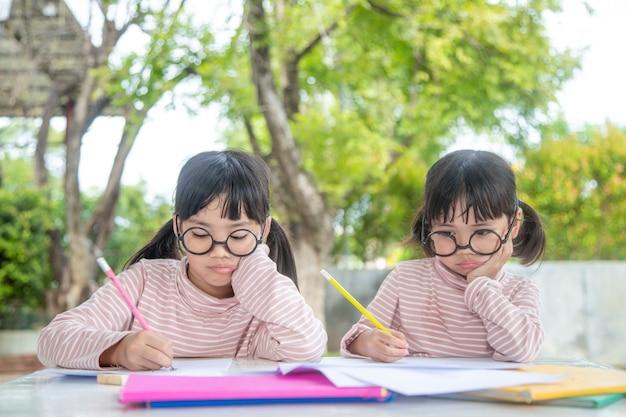 Двое азиатских детей вместе делают домашнее задание дома
