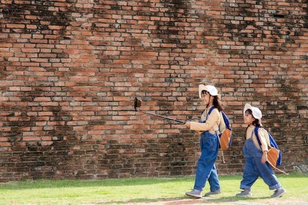 Две девочки азиатского происхождения - блогеры. трансляция в интернете. записывайте подписчиков видеоблога и блога. записывайте видео уроки для интернета. используйте камеру со штативом.