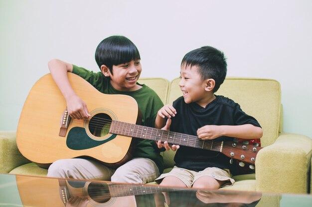 기타를 연주하고 집에서 함께 재미 두 아시아 어린이