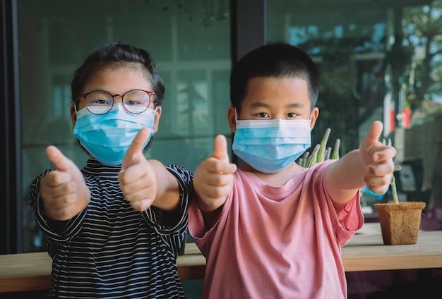 自宅で立っている保護フェイスマスクを身に着けている2人のアジアの子供たち