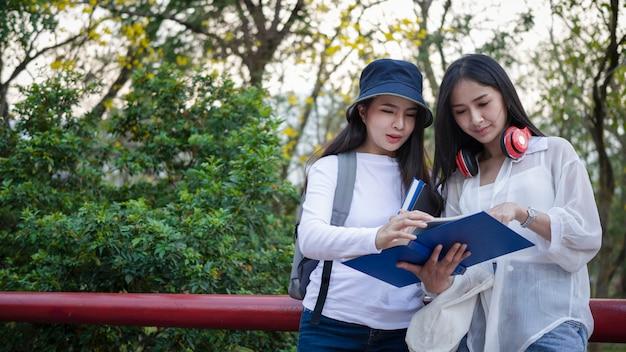 캠퍼스에서 함께 공부하는 두 명의 아시아 대학생.