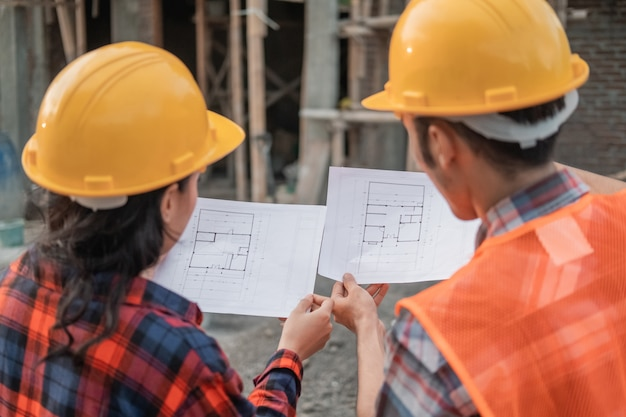 Two asian contractors standing in safety helmets holding the site plan building