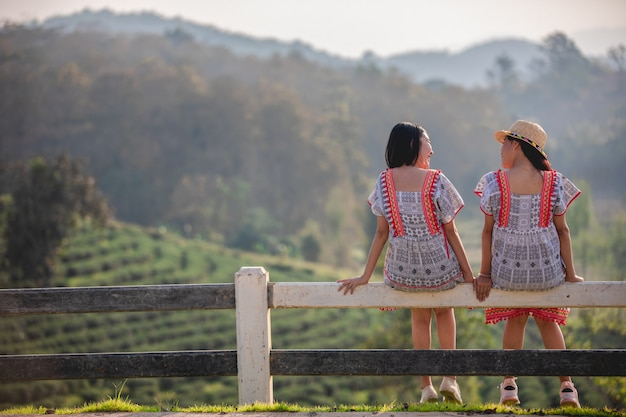 Two asian cute and young girls sitting on the garden fence on sunset
