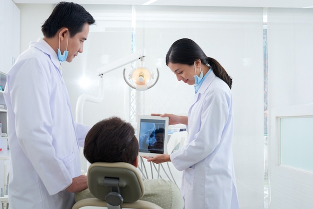Two asian dentists demonstrating patient jaw x-ray on tablet