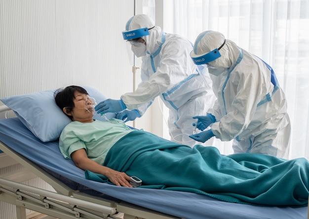두 명의 아시아 의사가 n95 마스크와 안면 보호대를 착용 한 ppe 슈트를 착용하고, 음압 실에서 코로나 바이러스 감염 환자와 함께 산소 마스크를 치료 및 사용합니다.