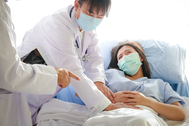 Two asian doctors examined the abdominal pain of a woman lying in a hospital bed. treatment of patients during the coronavirus epidemic. concept of medical service