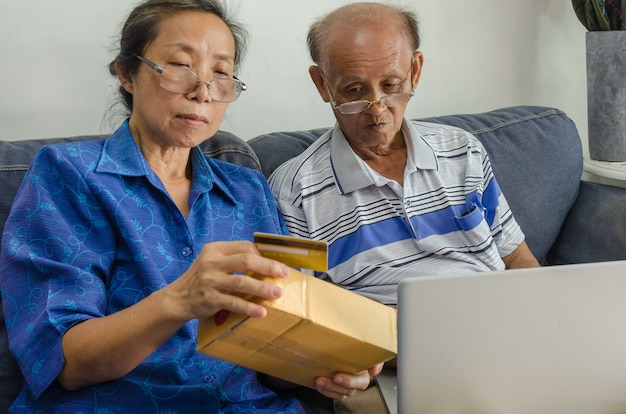 Two asian elderly people shopping online. senior holding credit card sitting on a sofa with laptop at home.