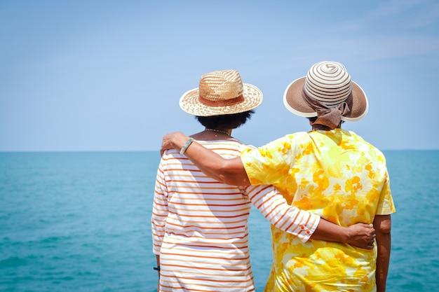 Две азиатские пожилые женщины, обнимающие друг друга, стоя и смотрят на море.