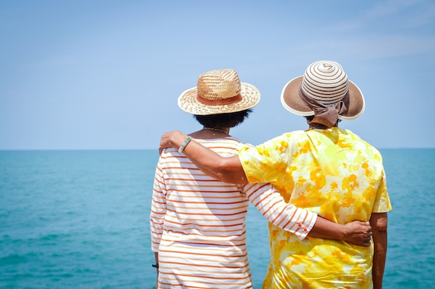Two asian elderly women hugging each other standing and watching the sea.