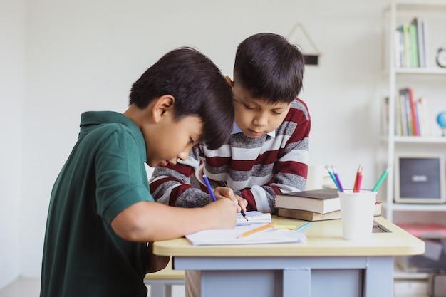 教室で一緒に勉強している2人のアジアの小学生