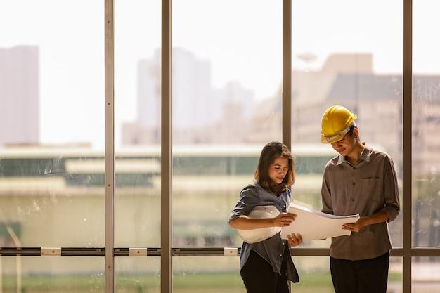 Два азиатских инженера, мужчина с желтым защитным шлемом и женщина с белым стоя и разговаривают возле стеклянной рамы высокой ненесущей стены на строительной площадке. оба смотрят на чертежную бумагу.