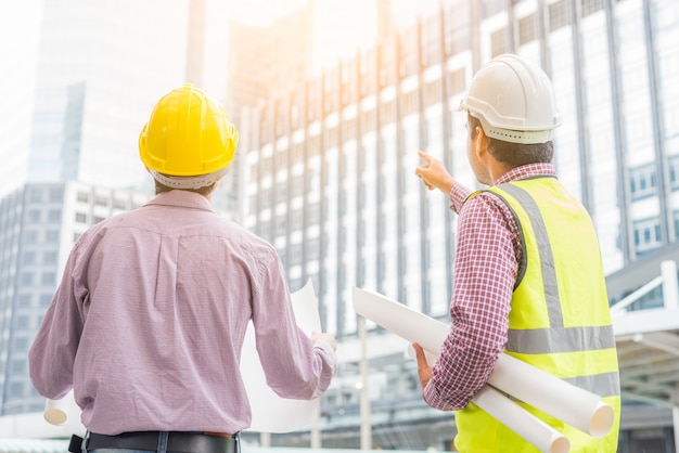 Two asian engineering checking plan on construction site.