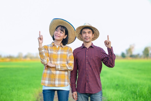 Two asian farmer man woman standing and raised up hand finger point to top at green rice farm