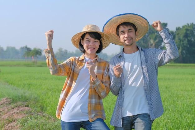두 명의 아시아 농부가 녹색 농장에서 웃고 행복한 포즈를 취합니다.