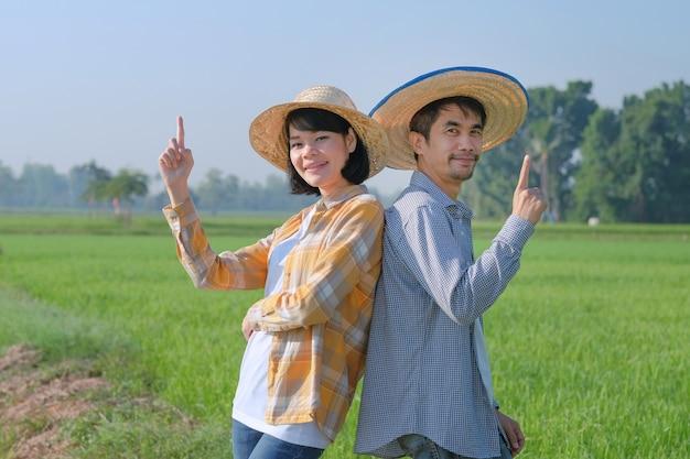 두 명의 아시아 농부가 녹색 쌀 농장에서 프레젠테이션을 위해 맨 위에 손가락으로 포즈를 취하고 있습니다. 부부 농부 개념입니다.