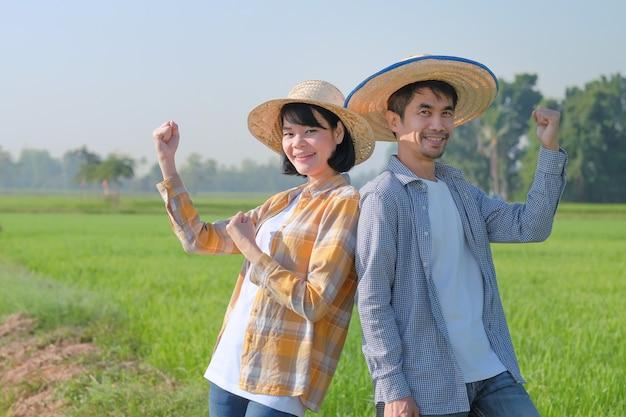 두 명의 아시아 농부가 녹색 쌀 농장에 서서 손을 들었습니다. 부부 농부 개념입니다.