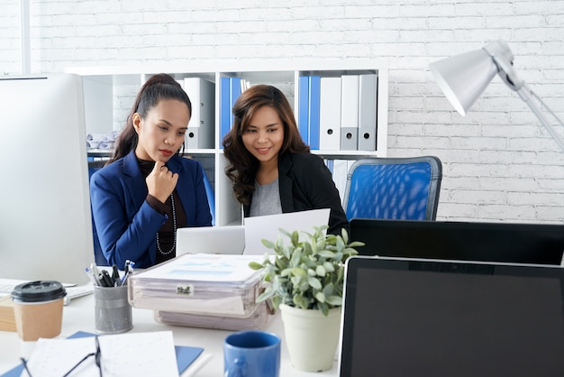 Two asian female colleagues sitting together in office and looking at document