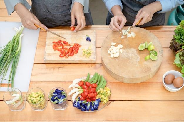 2人のアジア人女性が木の板にニンニクとトマトをナイフで切り、その地域にハーフライムのカウスリップフラワーバタフライピー、ネギ、卵を入れて昼食の準備をします。